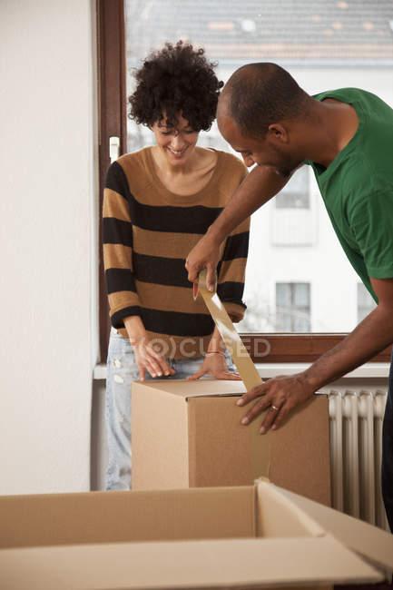 Веселая пара, работающая вместе, чтобы скотч движущейся коробке — стоковое фото