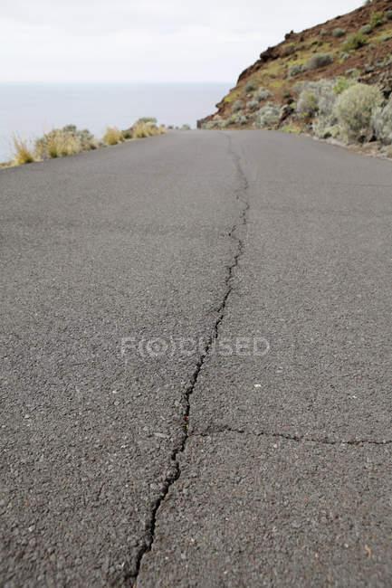 Поверхности уровня вид трещин в прибрежной дороге — стоковое фото