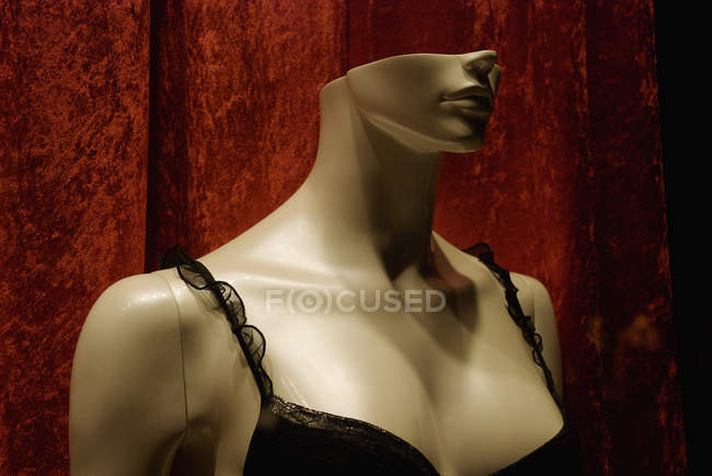 Mannequin wearing black lingerie over red curtain — Stock Photo