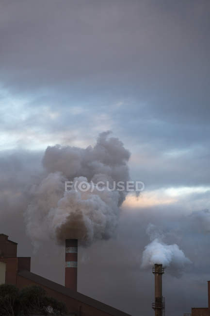 Fumo emesso dai camini contro il cielo nuvoloso — Foto stock