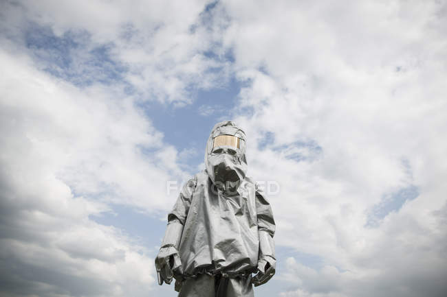 Person in radiation protective suit posing against cloudy sky — Stock Photo