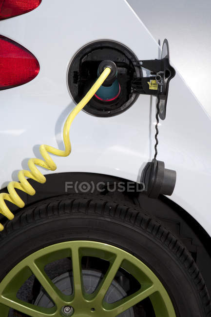 Electric charger connected to electric car recharging plug — Stock Photo