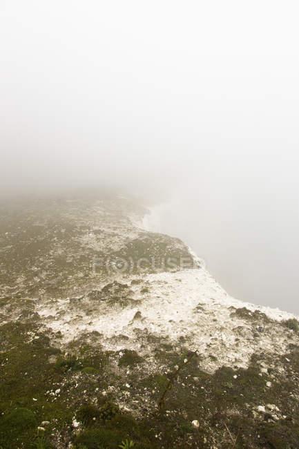 Vista panoramica della scogliera innevata nel tempo nebbioso — Foto stock