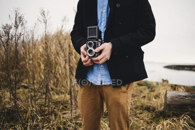 Midsection of man photographing through retro styled camera in park — Stock Photo