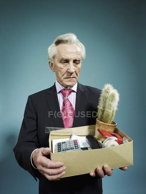 Senior man carrying a box of possessions after being fired — Stock Photo