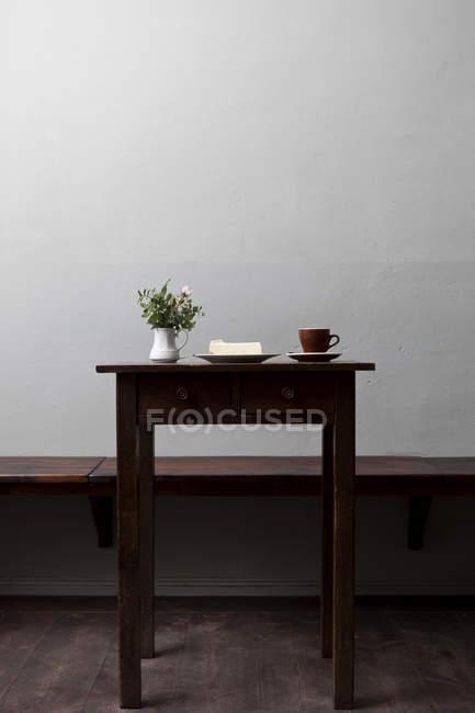 Ein Stück Käsekuchen mit einer Tasse Kaffee und Blumen auf dem Tisch im Café — Stockfoto