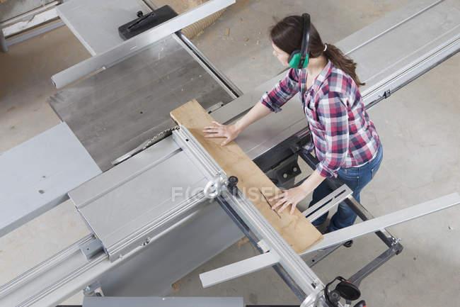 Female carpenter using sliding table saw in workshop — Stock Photo