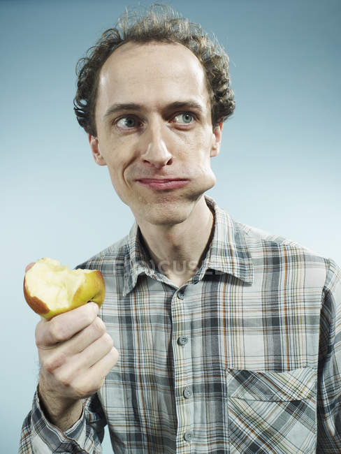 Homme avec une joue bombé avec un morceau de pomme — Photo de stock
