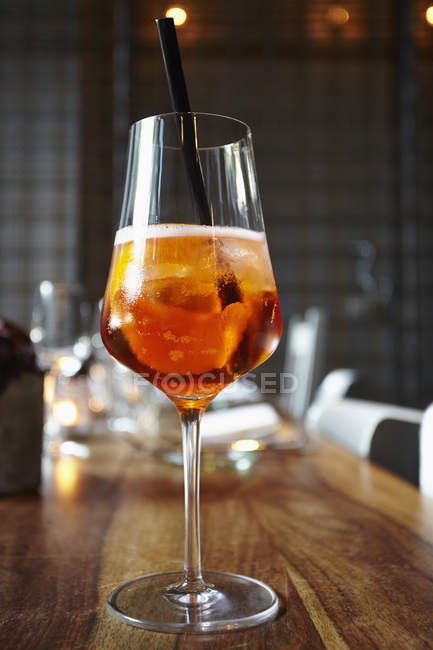 Nahaufnahme der Aperitif cocktail im Weinglas mit Stroh auf Holztisch — Stockfoto
