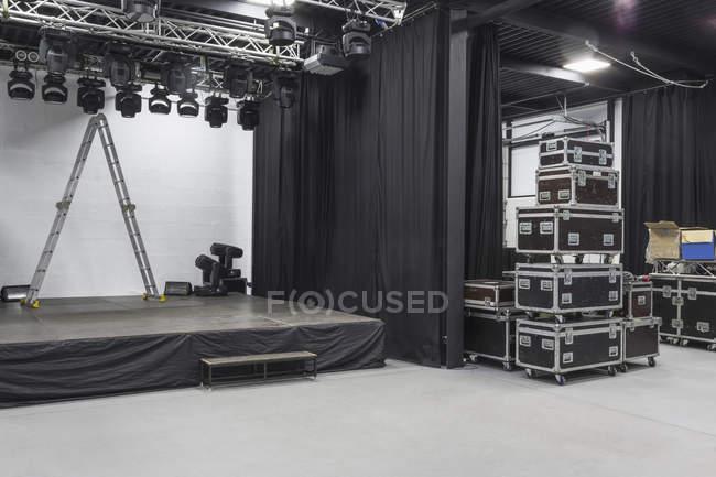 Vue intérieure du studio avec échelle sur scène et valises empilées avec équipement — Photo de stock