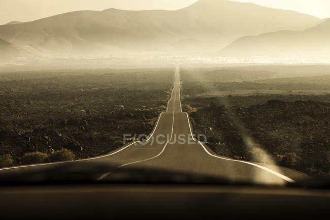 Коченню дорозі, що веде до гори в туманний краєвид — стокове фото