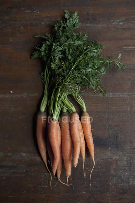 Directamente sobre la vista del montón de zanahorias en mesa rústica - foto de stock