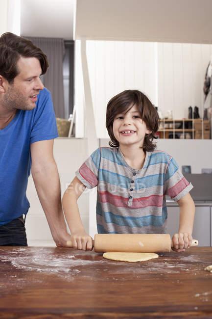 Portrait de garçon roulant pâte pour biscuits et père regardant — Photo de stock