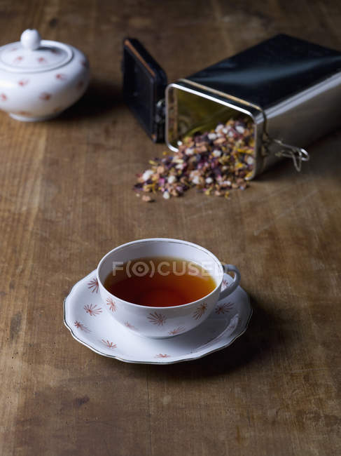 Tea cup with container of herbal tea on wooden table — Stock Photo