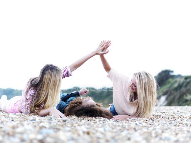 Una ragazza sdraiata tra due amici che le danno il cinque sopra la spiaggia — Foto stock