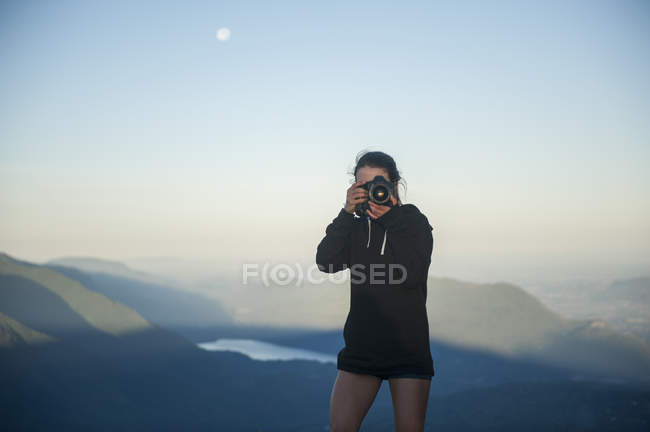 Woman photographing against misty mountain landscape — Stock Photo