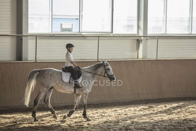 Vue latérale du garçon assis sur le cheval dans l'écurie de la formation — Photo de stock