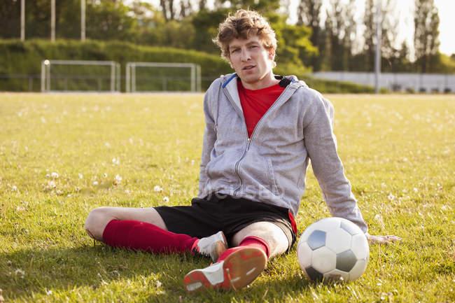 Портрет молодого футболіста, відпочиваючи на полі — стокове фото