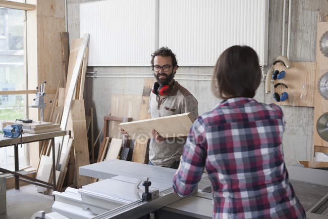 Male and female carpenters working together in workshop — Stock Photo