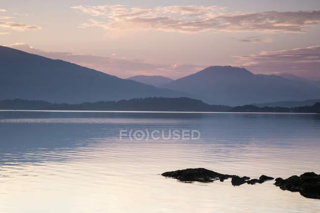 Idílica vista del apacible lago y las montañas durante el atardecer - foto de stock