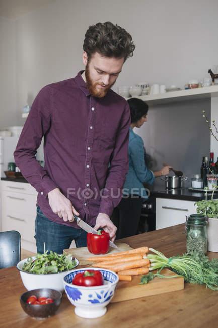 Jovem picar vermelho pimenta de sino na mesa da cozinha com a mulher no plano de fundo — Fotografia de Stock