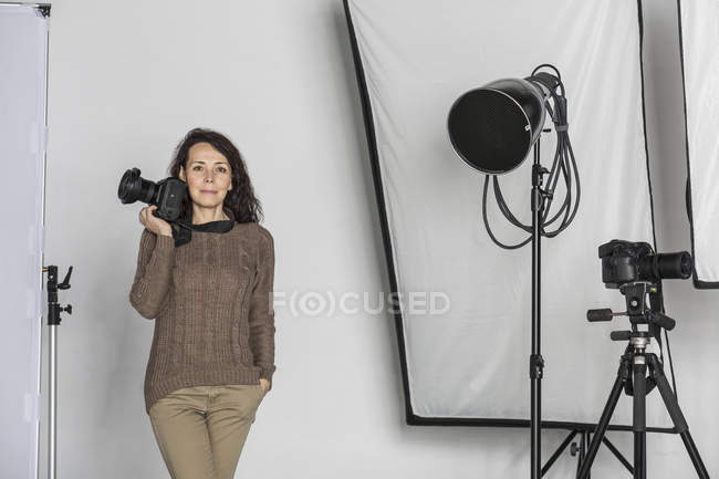 Portrait de photographe mature avec caméra en studio photo — Photo de stock