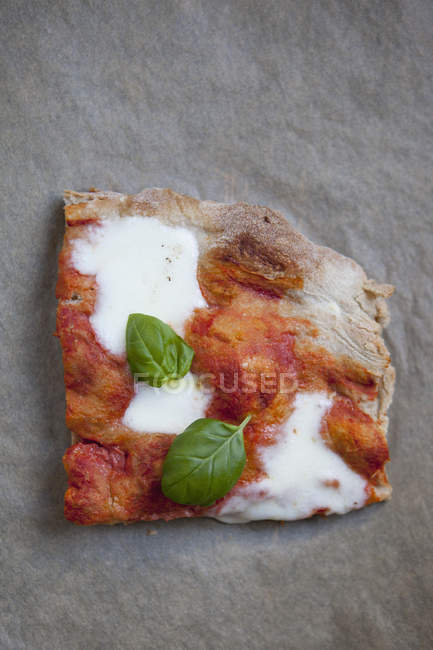 High angle view of pizza piece with mozzarella cheese and basil — Stock Photo