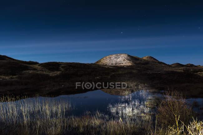 Tranquilo paisaje del estanque de la montaña contra el cielo al atardecer - foto de stock