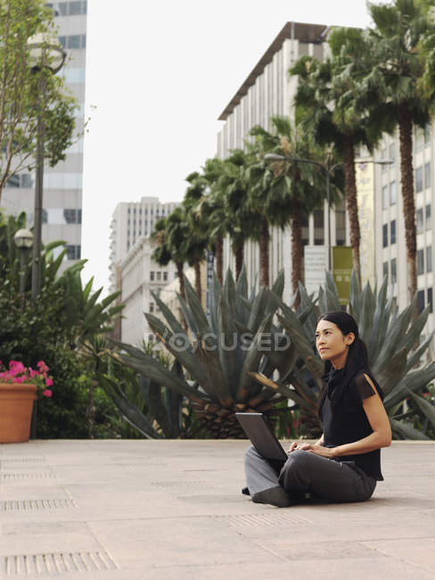 Businesswoman sitting cross-legged in courtyard of office complex and using laptop — Stock Photo