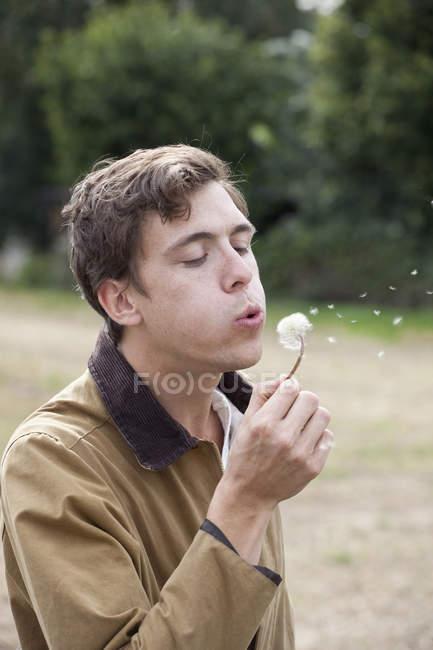 Homem soprando dente-de-leão e fazendo desejo na natureza — Fotografia de Stock
