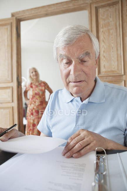 Senior man examining financial documents at home with woman on background — Stock Photo