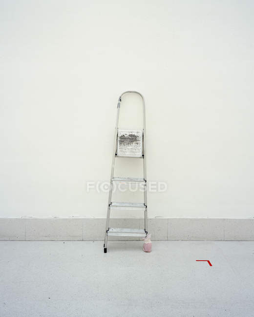Unstable ladder leaning on white wall — Stock Photo