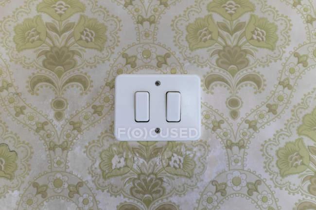 Light switch on ornate patterned wall — Stock Photo
