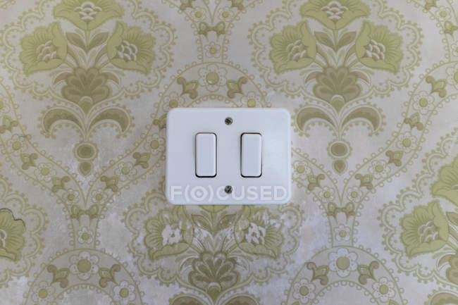 Light switch on ornate patterned wall — Stock Photo