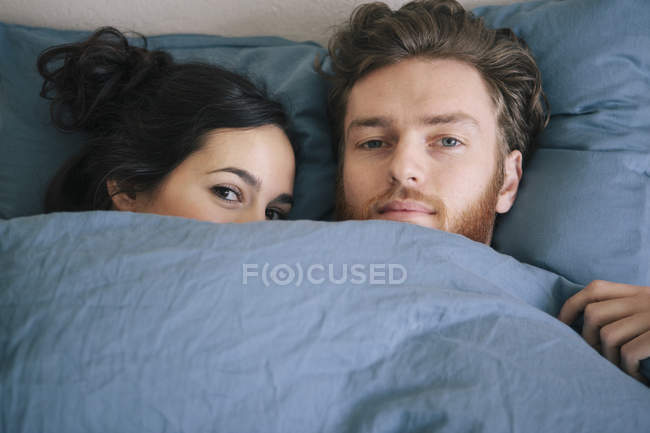 Portrait of loving young couple under duvet in bed — Stock Photo