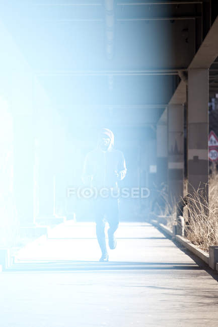 Man jogging on sidewalk under city bridge in sunlight — Stock Photo