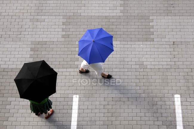 From above view of women with umbrellas walking through  parking lot — Stock Photo