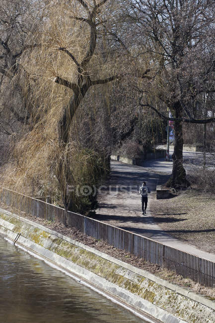 Jeune homme jogging à travers le parc de la ville — Photo de stock