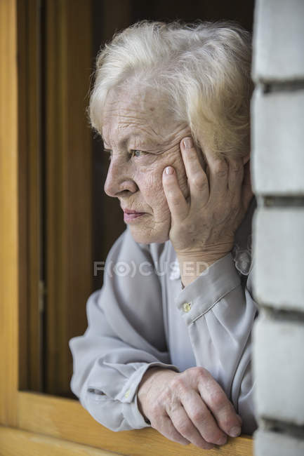 A senior woman leaning on a window sill, looking contemplative — Stock Photo