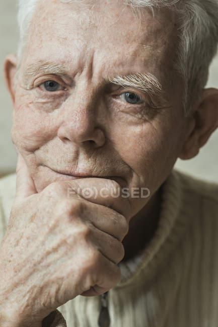 Gros plan portrait d'homme senior sérieux avec la main sur le menton — Photo de stock