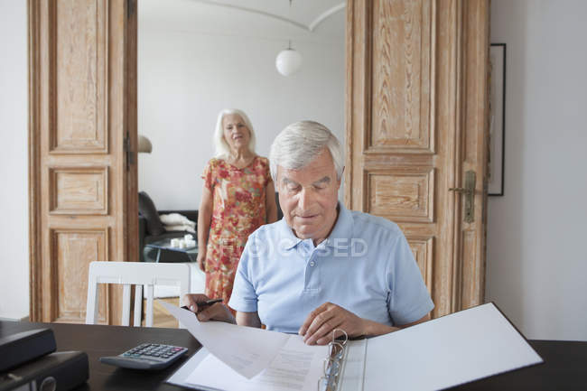 Senior man reviewing financial documents with woman on background at home — Stock Photo