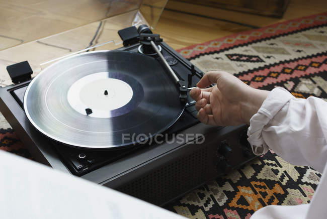 Crop female putting on record playing needle on vinyl at home — Stock Photo