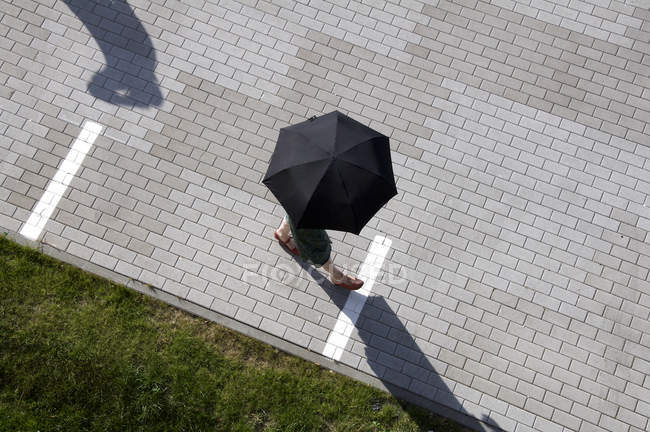 Woman under umbrella walking at alley — Stock Photo