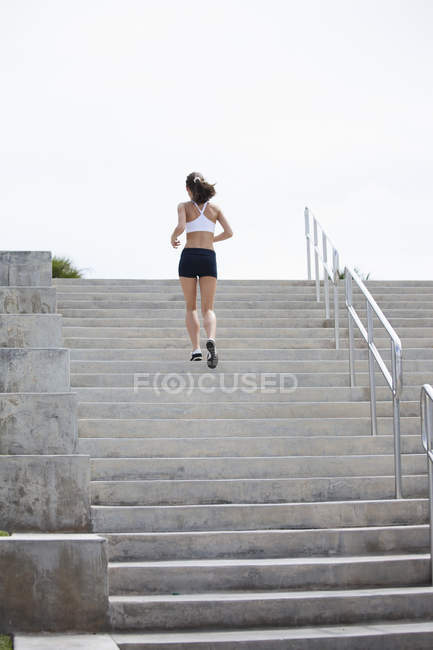 Rear view of girl jogging up steps — Stock Photo