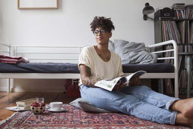 Giovane donna che tiene rivista nella camera da letto e che osserva via — Foto stock