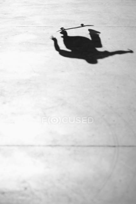 Shadow of person jumping on skateboard in park — Stock Photo