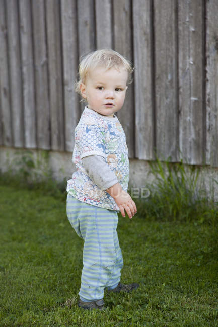Baby boy standing on grass and looking away — Stock Photo