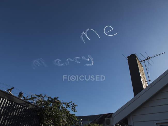Высокий угол вид Marry Me надпись, написаны пара тропы в голубое небо. — стоковое фото