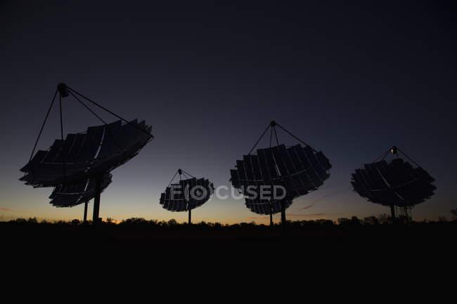 Силуэты солнечной блюд на электростанции против сумерках небо — стоковое фото