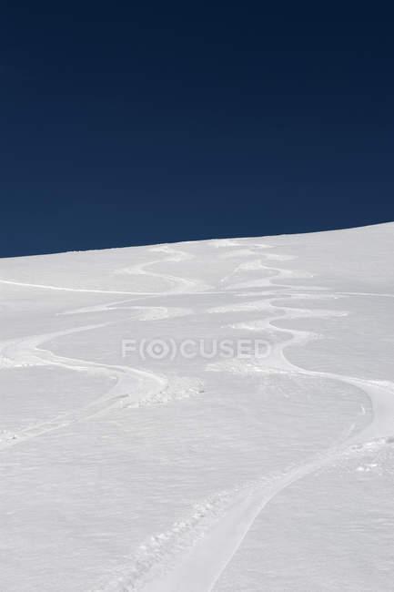 Ski tracks on snow slope against sky — Stock Photo